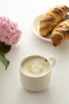 クロワッサンと一杯のコーヒー、ピンクのアジサイの花。