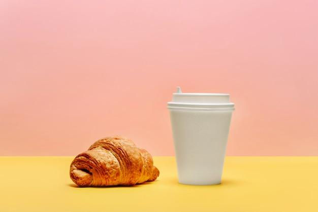 クロワッサンとコーヒーまたは紅茶用の白いカップ