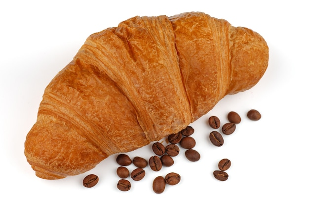 Круассан и кофейные зерна, изолированные на белом фоне