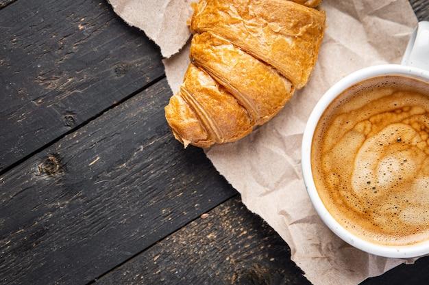 テーブルの上のクロワッサンとコーヒーの温かい飲み物の新鮮な食事の軽食コピースペース食品の背景