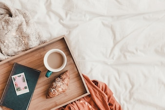 Croissant and coffee near book on bed