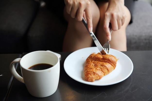 커피숍에서 먹기 위해 여자 손으로 크로와상과 커피