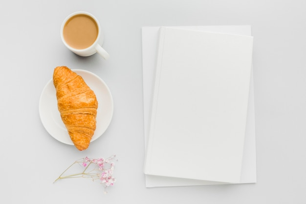 テーブルの上の本の横にあるクロワッサンとコーヒーのカップ