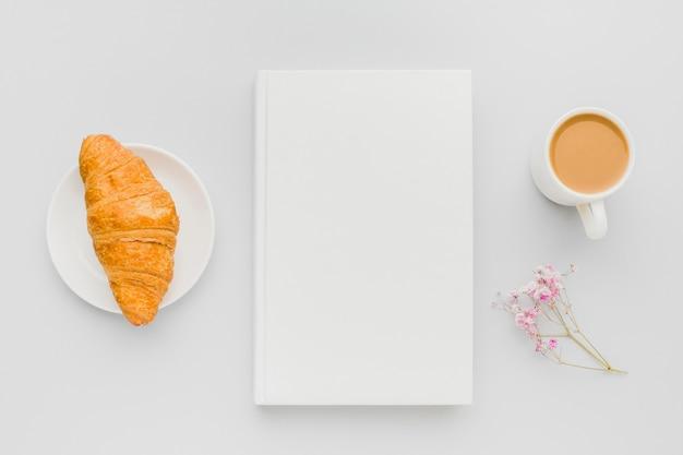 本の横にあるクロワッサンと一杯のコーヒー