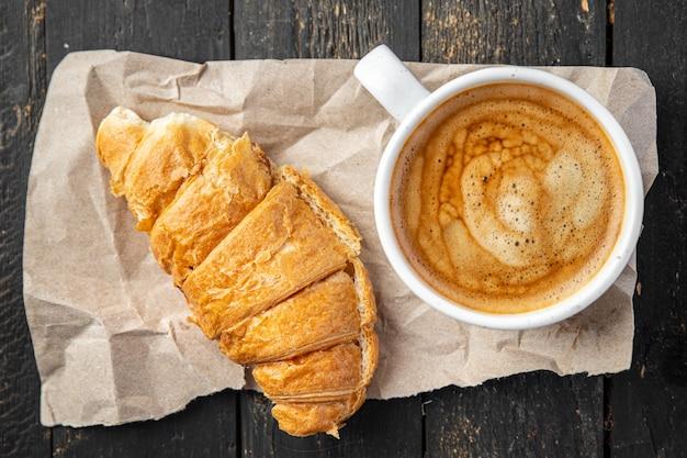 クロワッサンと一杯のコーヒーの新鮮な部分は、テーブルのコピースペースの食べ物で食事の軽食を食べる準備ができています