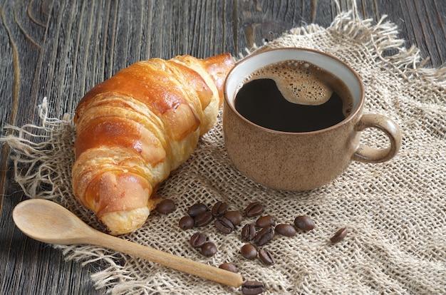 粗い生地で古い木製のクロワッサンとコーヒーのカップ