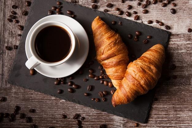 어두운 나무 테이블에 크루아상과 뜨거운 커피 한 잔. 훌륭한 아침 식사.
