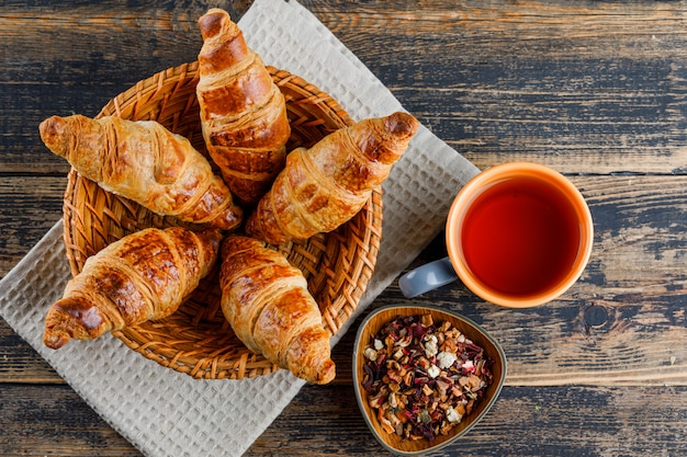 Croissant in basket with cup of tea, dried herbs flat lay on wooden and kitchen towel