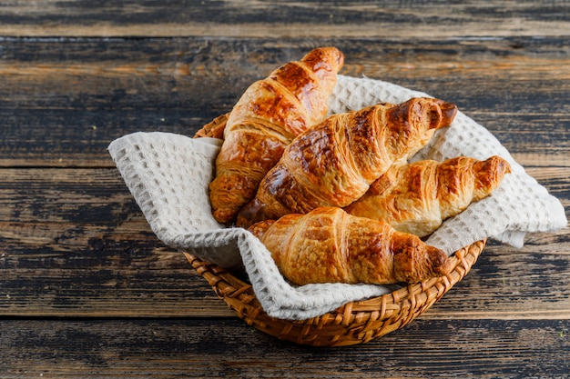 Croissant in a basket on wooden table, high angle view.