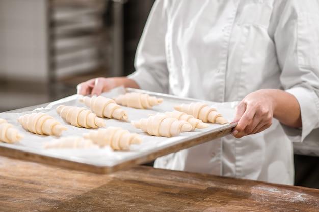 焼く前のクロワッサン。パン屋で焼くために準備された生のクロワッサンのトレイを持つパティシエの思いやりのある手、顔は見えません