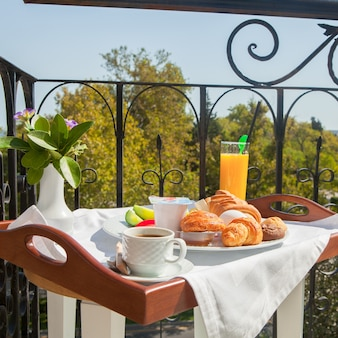 Croissant, boiled egg, orange juice breakfast on tray at balcony