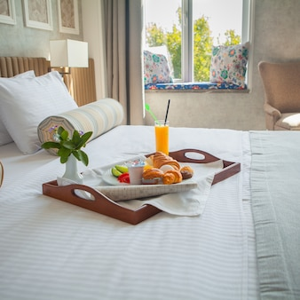 ホテルの部屋のベッドのトレイにクロワッサン、ゆで卵、オレンジジュース、ヨーグルトの朝食