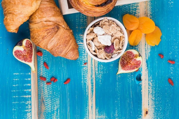 Croissant bread; fig fruit; corn flakes and dry apricot over wooden textured backdrop