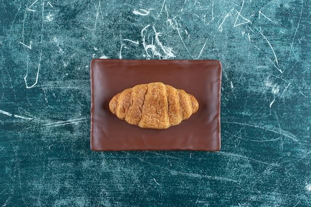 Croissant su un piatto marrone, sullo sfondo blu. foto di alta qualità