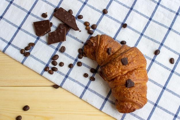 キッチンナプキンと木製の背景にクロワッサン、コーヒー豆、チョコレート。上からの眺め。