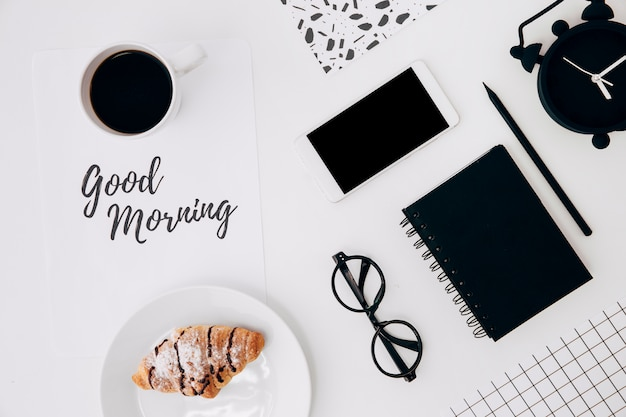 Croissant and coffee cup with good morning message on paper and office stationaries on white desk