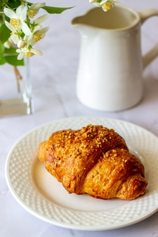 A croissant and coffee on a marble surface