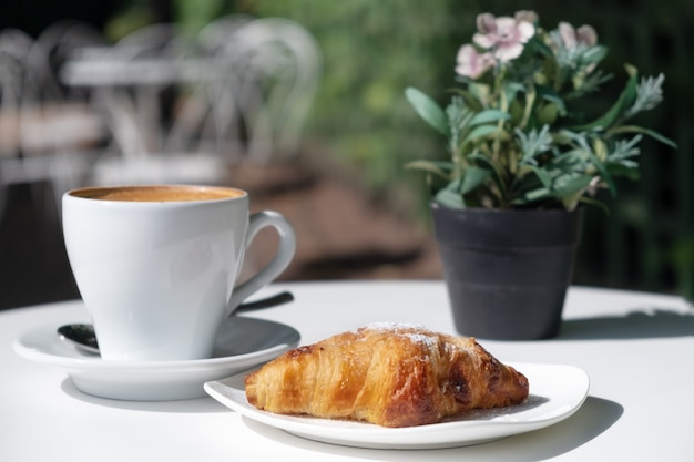 Croissant,cup of coffee,flowers on table in cafe outdoors in street in sunny weather.idea of french traditional breakfast in open air