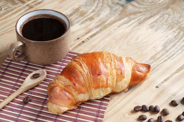 Croissant and cup of coffee on an old wooden