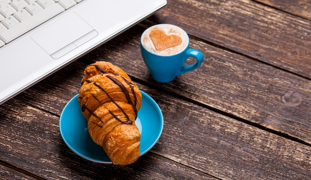 Croissant and cup of coffee with laptop on wooden table.