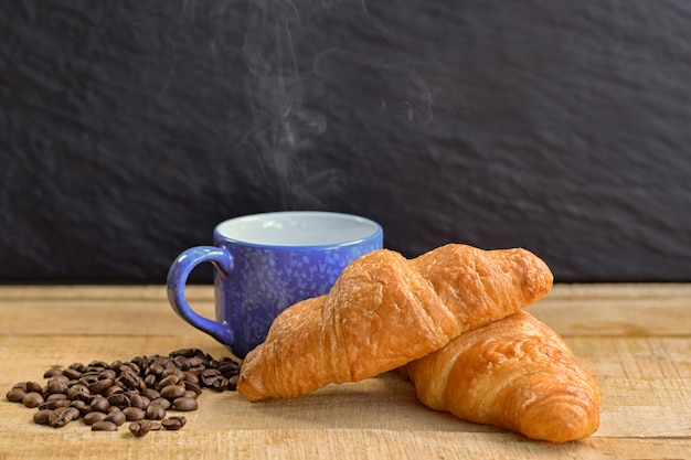 Croissant and cup of coffee on wooden table