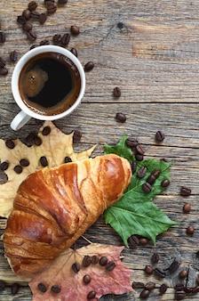 クロワッサン、一杯のコーヒーと古い木製のテーブル、上面図の紅葉