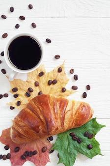 クロワッサン、一杯のコーヒーとテーブルの上の紅葉、上面図