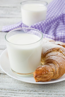 Croissant on dish with milk on old wooden table for breakfast background.