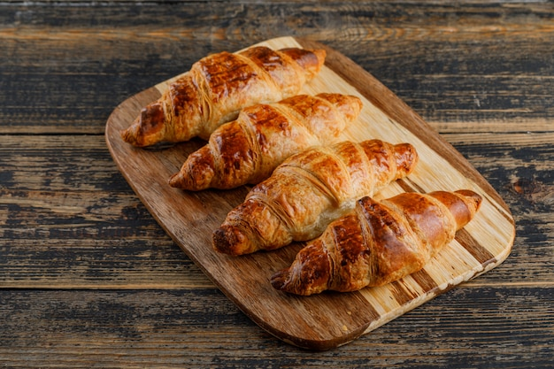 Croissant high angle view on wooden and cutting board