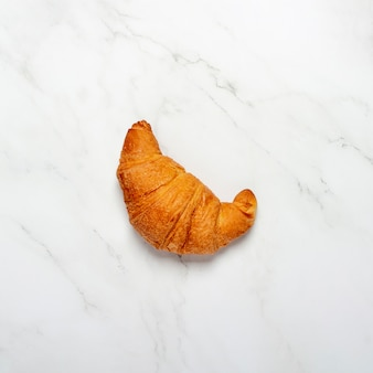 Croissant on a marble surface. concept bakery, pastries, france, breakfast. flat lay, top view