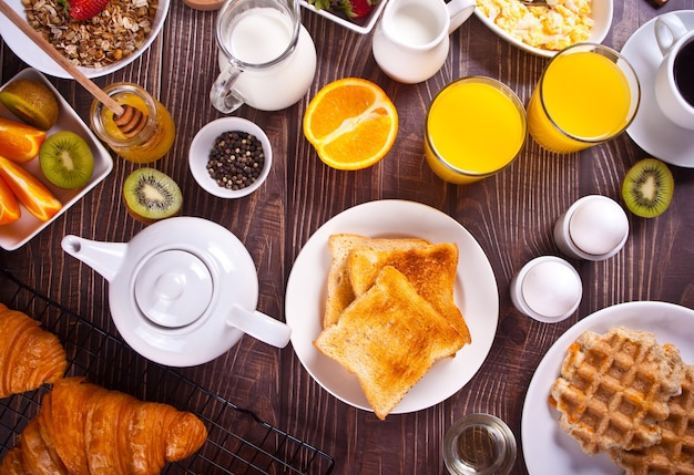 Croissant, muesli, toasts, fruits, eggs, waffles and cup of coffee