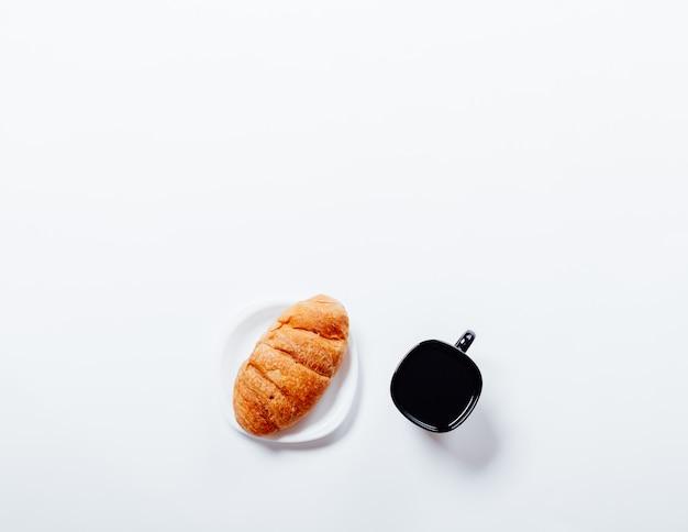 ソーサーと白いテーブル、トップビューでコーヒーの黒いカップのクロワッサン