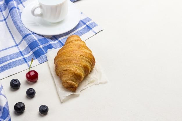 白と青の市松模様ナプキンにクロワッサン。テーブルの上のブルーベリー。トップビュー、白い背景。コピースペース