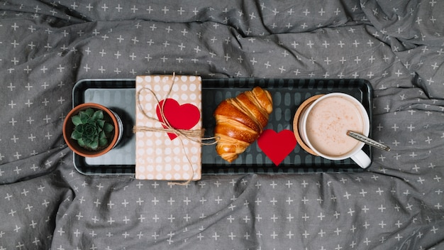 Croissant, ornament heart, cup of drink, plant and gift box on tray