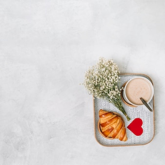 Croissant, ornament heart, plants and cup of drink on tray