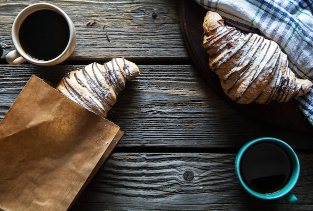 Croissant in a paper bag with a cup of coffee. breakfast, snack,