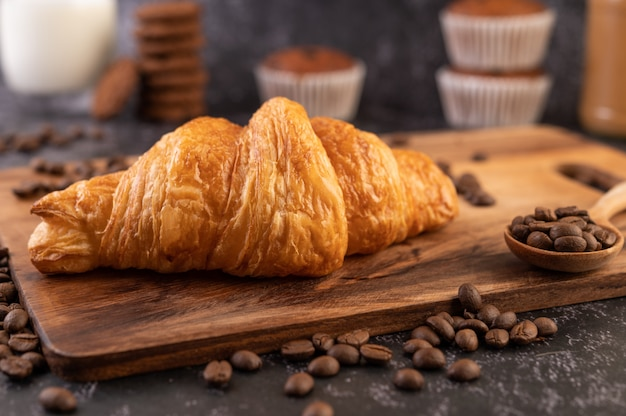Croissant placed on a wooden platform with coffee beans on a black cement floor.