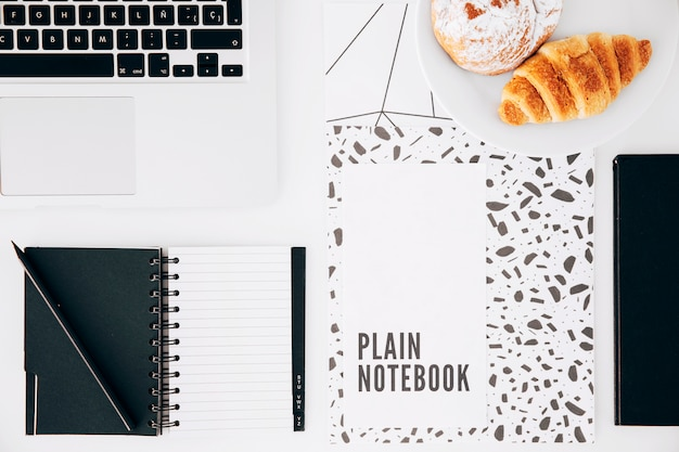 Croissant; plain notebook; laptop; pencil and spiral notepad on white desk