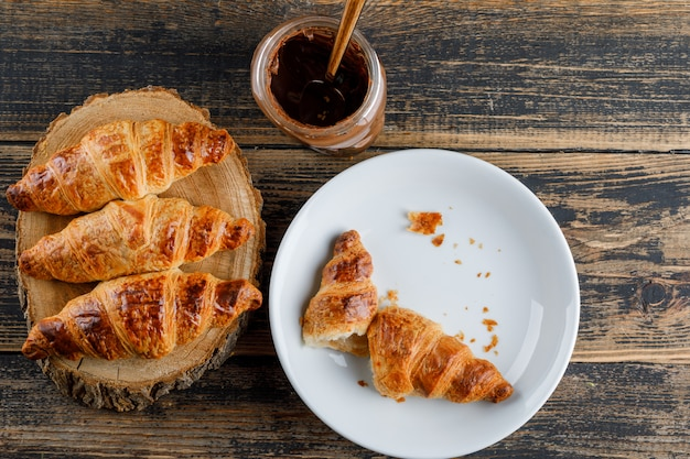 Croissant in a plate with chocolate cream flat lay on wooden and cutting board