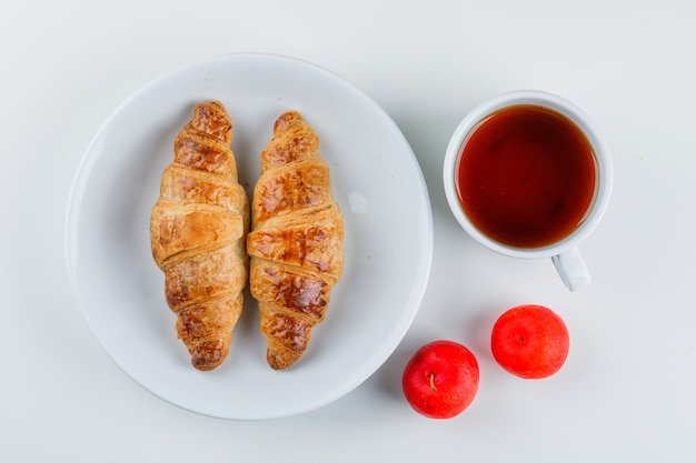 Croissant in a plate with plums, tea flat lay