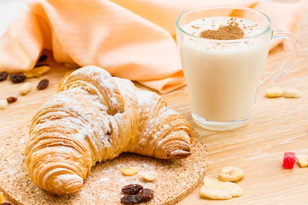 Croissant in powdered sugar and glass of milk wiht heart from cinnamon on a wooden table