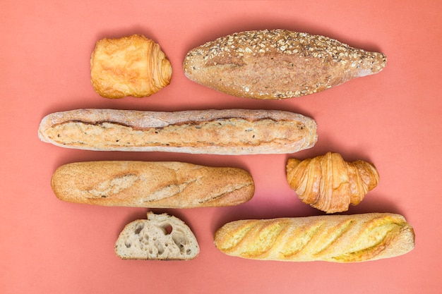 Croissant; puff pastry; loaf and baguette breads on colored backdrop