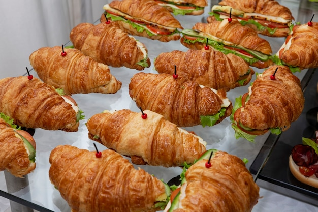Сэндвич с круассаном на фуршетном столе. питание для деловых встреч, мероприятий и торжеств.