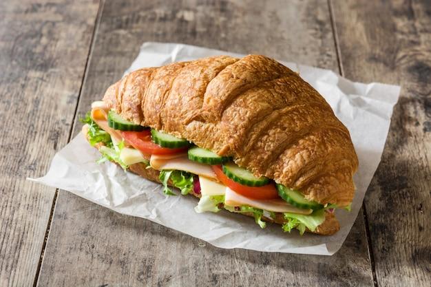 Круассан бутерброд с сыром, ветчиной и овощами на деревянный стол