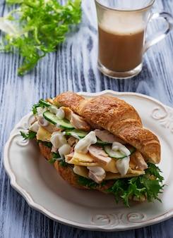 Croissant sandwich with chicken, cheese, cucumber