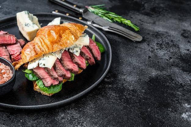 블루 치즈와 필레 미뇽 안심 고기 스테이크와 크로와상 샌드위치. 검정색 배경. 평면도. 공간을 복사하십시오.