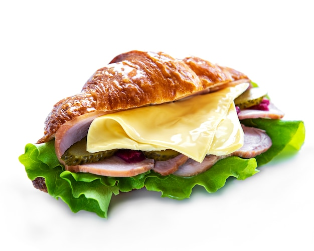 Croissant sandwich with ham, cheese and lettuce on a white surface