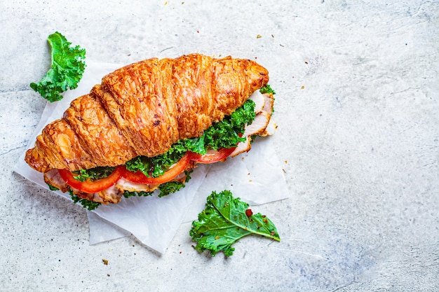 Croissant sandwich with meat, vegetables and green kale, white background. breakfast food concept.
