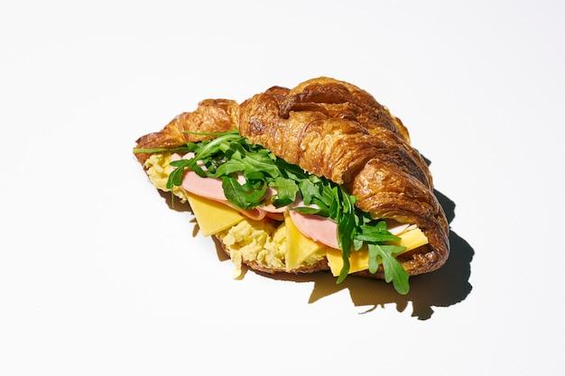 Сэндвич с круассаном с мортаделлой, сыром, рукколой и яичницей. жесткий свет. белый фон