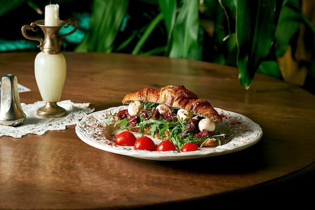 Сэндвич с круассаном с моцареллой, рукколой, вялеными помидорами на деревянном фоне